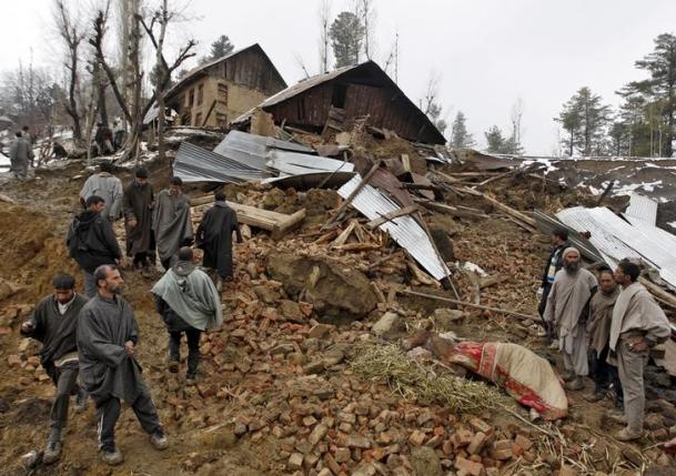 Police stand amidst the rubble after a hillside collapsed onto a house at Laden