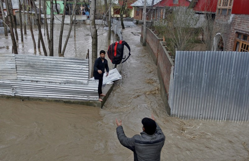 A man throws his belongings towards another to be moved to a safer place at a flooded neighbourhood after incessant rains in Srinagar